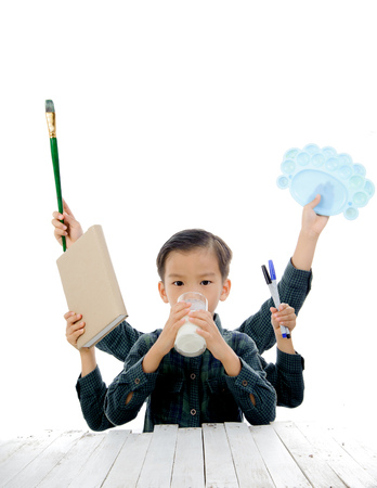 pallette: Jeune gar�on asiatique avec de multiples livres de prise de main, marqueur, pinceau, palette et boire du lait isol� sur blanc. Concept de l'�ducation.