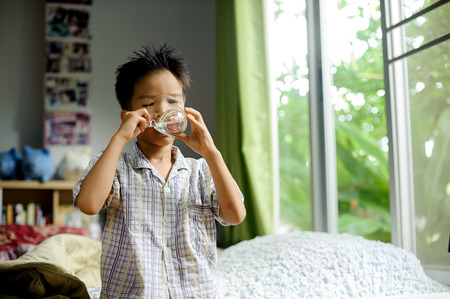 kid room: Close up young asian boy drink water from transparent glass after wake up in the morning from the bed