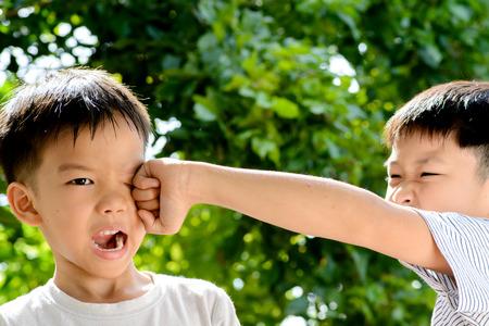 puÑos: Muchacho asiático joven que fue golpeado por su hermano delante de fondo bokeh verde de la hoja del árbol Foto de archivo