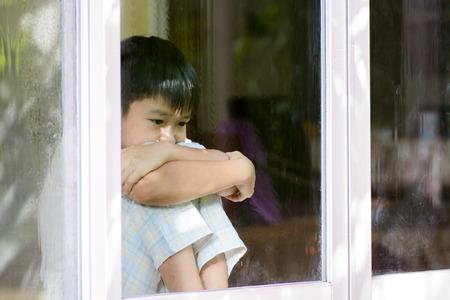 ni�os pensando: Muchacho asi�tico sentarse junto a la ventana despu�s de la lluvia en la casa se vea triste y solo concepto. Foto de archivo