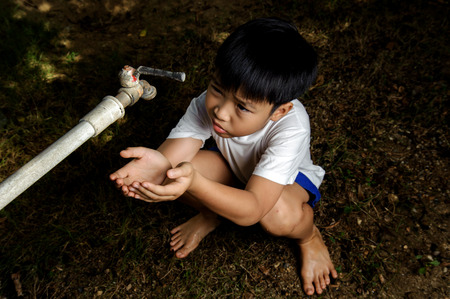 Dark color tone Asian boy waiting for water from faucet on hot and dry empty land. Water shortage concept. Stock Photo