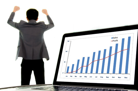 sucess: Focus on laptop monitor showing growth chart of sales and profit, out focus headache man in suit look sucess and happy. Win and gain business concept.