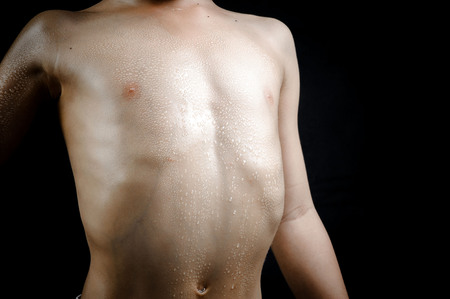 boy body: Close up on skin body muscle and sweat drop on young strong Asian boy body after heavy excercise