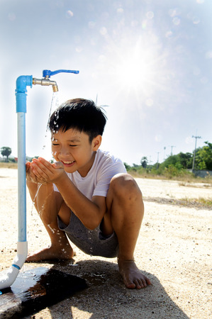 Close up Asian boy open metal blue water faucet on hot and dry empty land. Water shortage concept.