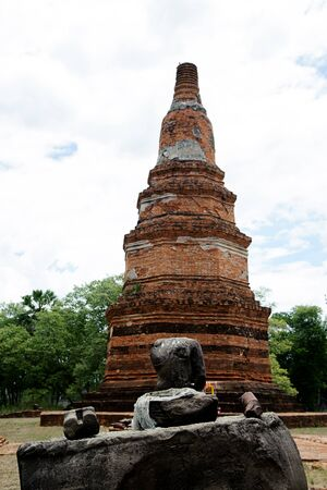 budda: Budda statue in front of red brick pagoda in public area in Thailand without head because of thife . Stock Photo