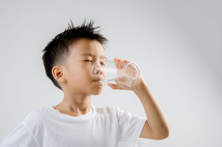 白いシャツのアジアの若い男の子は、新鮮な水の入ったグラスを手に保持し、飲みます。概念水の日。