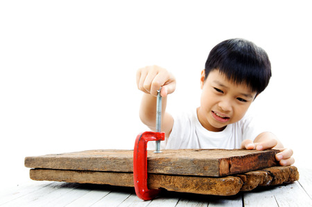 two piece: Young asian boy using red clamp to hold two piece of old wood on white background.