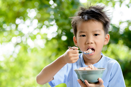 Thin focus on young Thai boy eating organic red rice with high zinc by stainless spoon on green bokeh background. Rice is a major consumption of Thai people.
