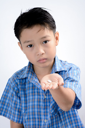 Young asian boy taking table medicine to solve fever. Heath and hospital concept Imagens