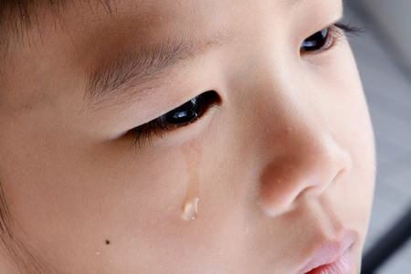 ojos llorando: Cierre en lágrima de ojo joven muchacho asiático que llora de su dolor. Foto de archivo
