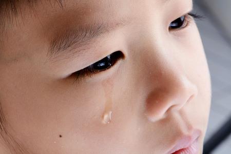 lacrime: Primo piano su lacrima dai ragazzo occhio asiatico che grida dal suo dolore.