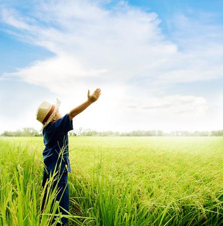 タイの伝統的な青いシャツと麦わら帽子感覚のアジアの若い男の子リラックス米に関するフィールドである前部の収穫します。
