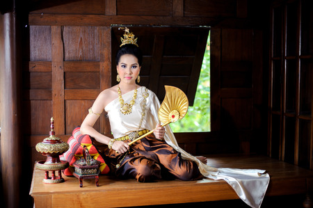 gold house: Portrait young Thai girl in old fashion costume at old Thai wooden house
