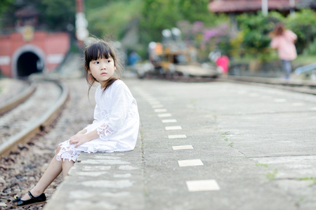 comming: Portrait little cute Asian girl sit beside railway and wait for the train comming with tunnel background