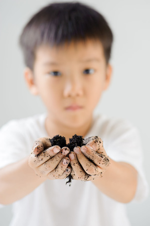 asian gardening: Close up with thin focus on little hand of young asian boy with black soil and dirty after gardening. Ecology and earth day concept