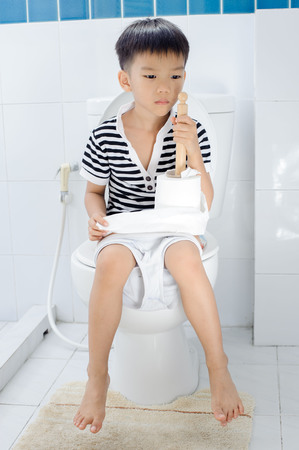 pis: Muchacho asiático joven se sienta en lavabo blanco en el baño