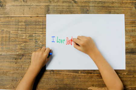 cute kids: Focus on kid hand use crayon color write text on white paper. I love dad. Stock Photo