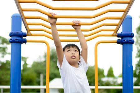 barra de bar: Joven muchacho asi�tico colgar la barra amarilla por su mano de hacer ejercicio a cabo parque puerta