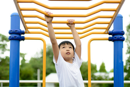 exercises: Young asian boy hang the yellow bar by his hand to exercise at out door playground