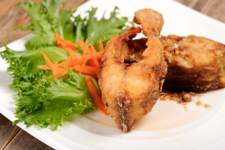deep fry: Thai food deep fry fish with vegetable on white dish on wood table