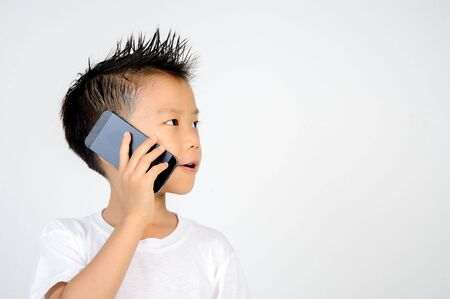 Young asian boy hold and talk by black cell phone on white background