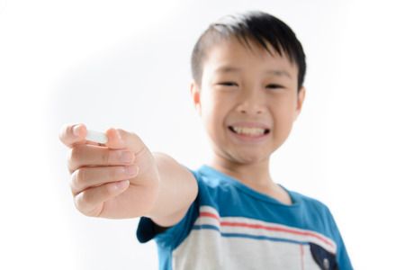 Clouse up on white tablet medicin in hand and blur face of young Asian boy on white background. Health care concept