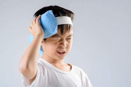 アジアの若い男の子, 頭痛が不幸な感じし、白い背景の上の痛みを軽減する彼の頭を青の氷パックを使用