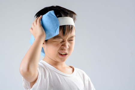 Young asian boy feel unhappy because of headache and use blue ice pack with his head to reduce the pain on white background
