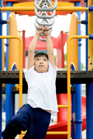 Young asian boy hang and play with steal bar with fun at out door playground Imagens
