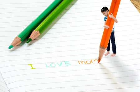 Close up on macro size effect, Young Asian boy write on the note book by color pencil. I love mom. Mother day concept