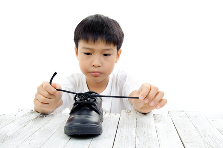 Young Asian boy lacing black leather shoe rope by his own on green tree background. Imagens