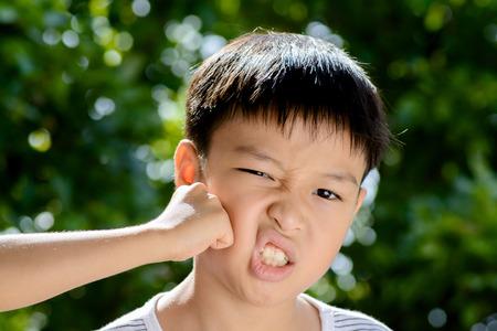 occhi tristi: Giovane ragazzo asiatico � stato colpito dal fratello di fronte a sfondo verde bokeh da foglia albero Archivio Fotografico