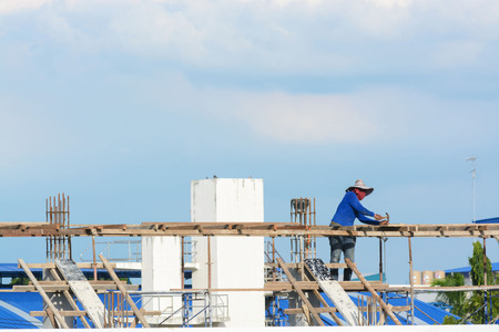 hot day: Worker without helmet construct a white building under the day light Stock Photo