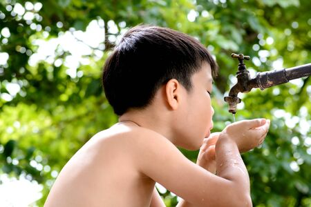 important: Close up young asian boy take water from old and grunge faucet on green bokeh background. Water shortage and earth day concept.