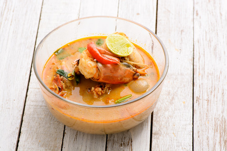 sour grass: Tom Yum Goong - Famous and very delicious food that hot and spicy soup with shrimp that could easily found in most of resturant in Thailand, serve in glass bowl. Thai Cuisine