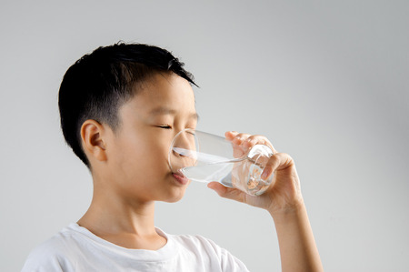 Asian young boy in white shirt hold glass of fresh water in hand and drink. Concept water day.