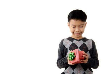 look inside: Young boy carry and look inside gift box in his hand. Christmas and new year concept.