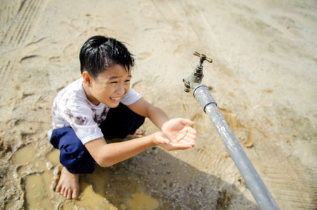 Close up thin focus on old faucet that Young Asian boy waiting for water on hot and dry empty land. Water shortage and drought concept. Stock fotó