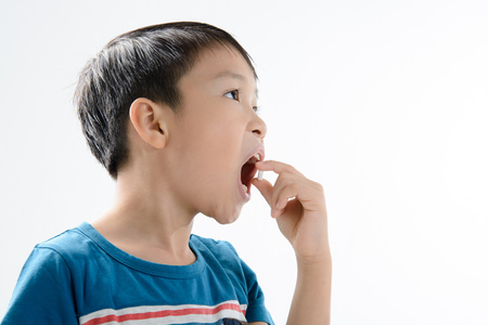 Young Asian boy taking white tablet medicine in to mouth by himself on white background. Health care concept. Stock Photo