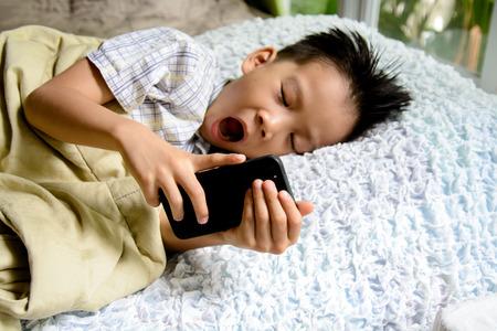 白いベッドの上の携帯電話を使用して眠そうな若いアジアの少年の手の薄いフォーカス