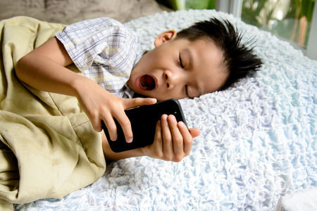 Thin focus on hand of sleepy young Asian boy using cellphone on white bed