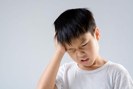 niños enfermos: Muchacho asiático joven que se siente infeliz a causa de dolor de cabeza en el fondo blanco