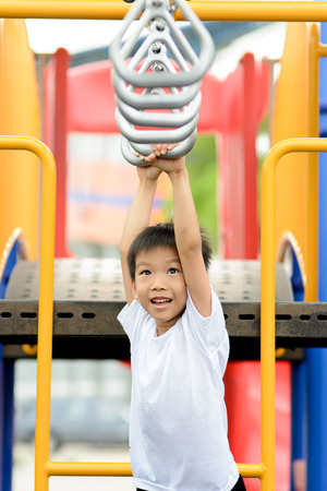 out door: Young asian boy hang and play with steal bar with fun at out door playground Stock Photo