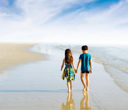 familias jovenes: Hermana hermano holding pie la mano en la playa en la costa tropical Foto de archivo