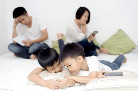 familias unidas: Familia en sala de estar usando smartphone y tablet dispositivo de cada uno por separado. Concepto de red social. Foto de archivo