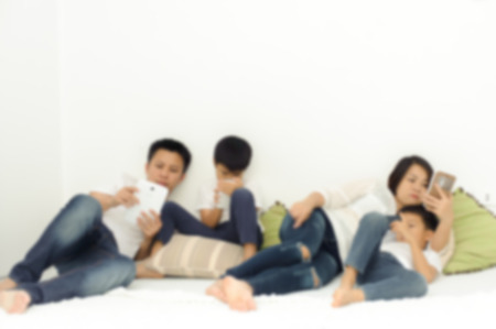 out of focus: Out focus. Family in living room using smartphone and tablet device each one separately. Social network concept.