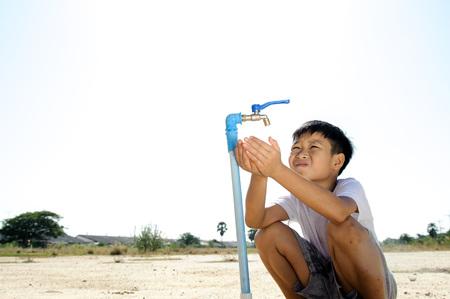 間近でアジアの少年は、暑くて乾燥した空の土地に金属青い水栓を開きます。水の不足のコンセプトです。 写真素材