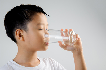 chinese drinks: Asian young boy in white shirt hold glass of fresh water in hand and drink. Concept water day.