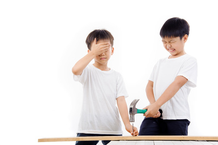 hammer and nails: Asian older brother do not careful and close his eye and use hammber to hit the nail that his brother holding.