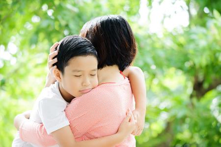 hug: Asian boy happy and hug his mother in garden on green tree bokeh background.